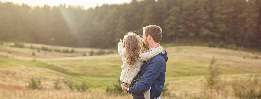 Daytime view of a father holding his young doughter as she points to the sun rising behind trees at the edge of a rolling field