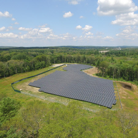 Daytime aerial view of a Blue Cross Blue Shield of Massachusetts solar farm in a wooded area