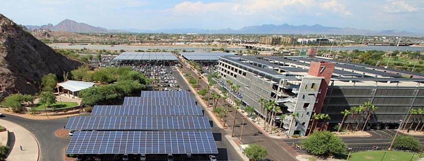Daytime aerial view of Arizona State University parking areas showing solar carport installations and panels on the top level of a parking garage