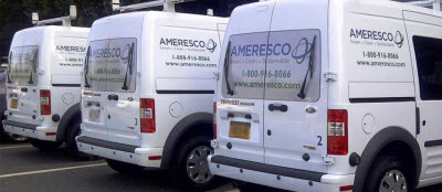 Daytime view of three Ameresco-branded minivans parked outside a facility
