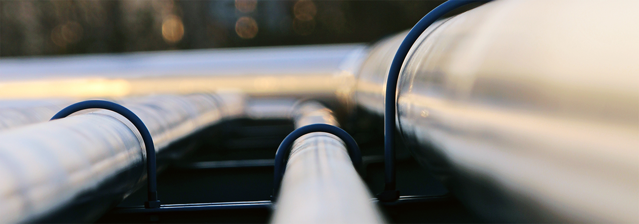 Daytime closeup of pipes that stretch back toward an energy plant in the distance