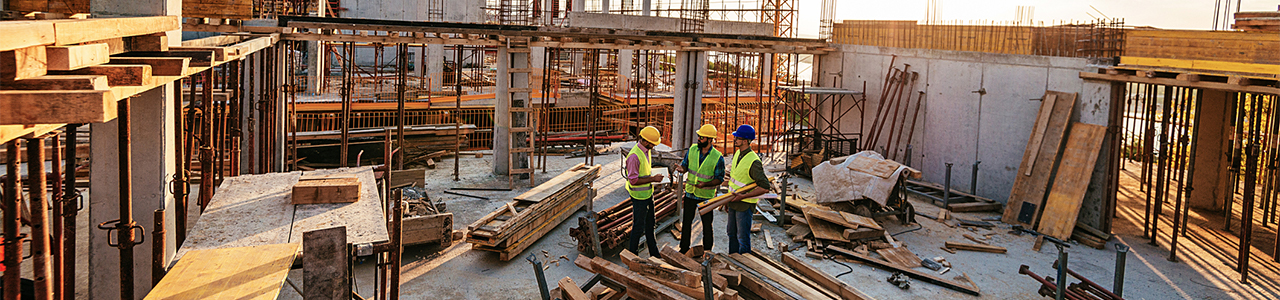View of three workers in the middle of a building under construction, standing on an upper floor