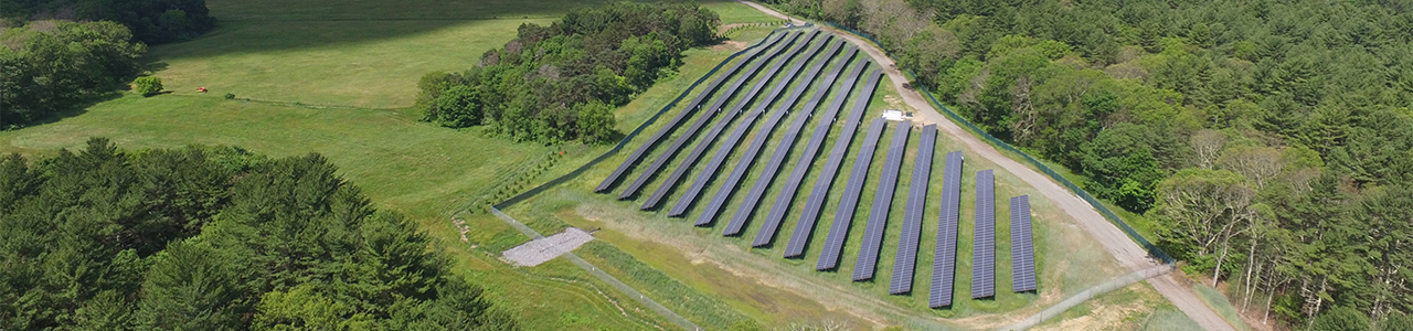 Daytime aerial view of a solar farm in a forested area