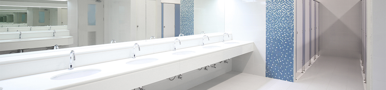 Interior view of a restroom in a large building showing a row of sinks with touchless, high-efficiency controls