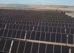 Daytime aerial closeup of rows of solar panels in a solar farm in San Joaquin County