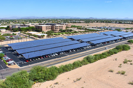 Daytime aerial view of large solar car port canopies on the campus of Arizona State University