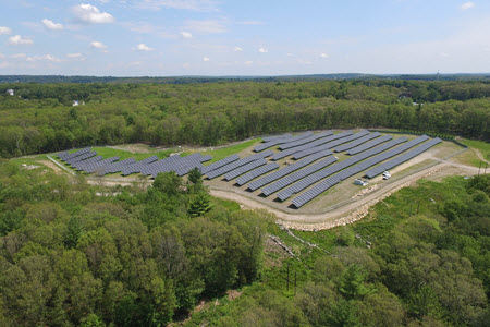 Daytime aerial view of a solar farm in a wooded area