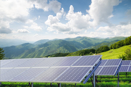Daytime view of solar panels mounted in arrays on a hillside with mountains in the background