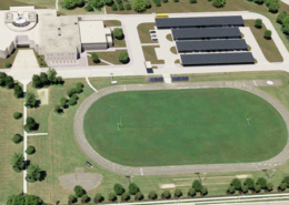 Aerial view of John Paiul II Catholic Secondary School in Ontario, Canada with rendered solar car ports and battery storage systems